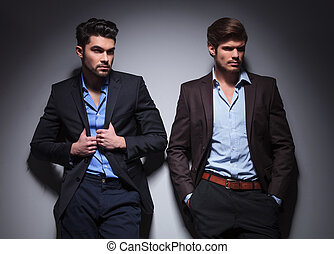 two male models looking away, one with hands in pockets, one...