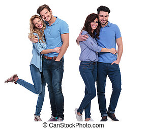 two happy couples of young casual people standing embraced...