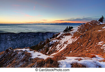 Sunset in winter mountains landscape with forest