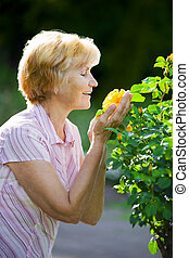Sentimentality Mature Old Lady Smelling Yellow Flower -...