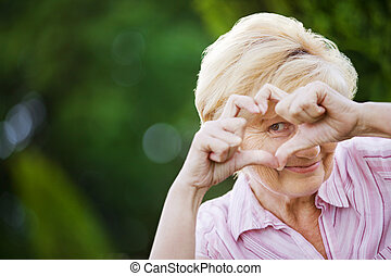 Positivity Happy Funny Senior Woman Showing Symbol of Heart