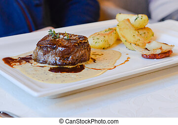 Beef medallion served with fried potatoes in restaurant on...