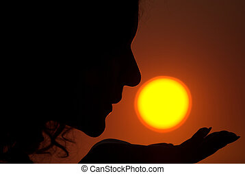 Sun kissing - Young female is kissing the Sun during sunrise