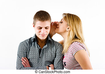 young woman whispering a secret to a man's ear