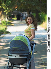 Young mother walks in the park with baby carriage