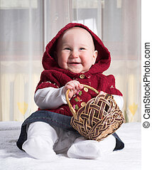 Smiling baby with basket - Smiling baby is sitting in bed...