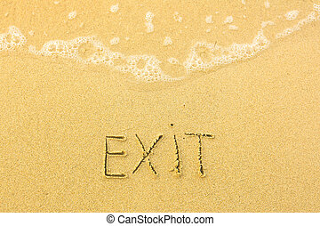 Exit - written in sand on beach texture - soft wave of the sea.