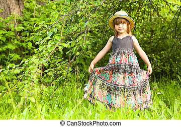 Little lovely girl posing in a straw hat in the park