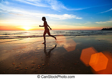 Silhouette of a young woman jogger at sunset on the seashore.