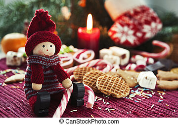 Wooden smiling doll with sweet striped candy canes on...