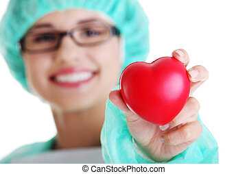 Smiling female doctor or nurse holding heart
