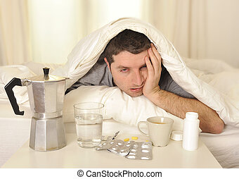 Man with headache and hangover in bed with tablets -...
