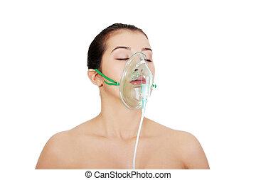 Diseased female patient wearing a oxygen mask