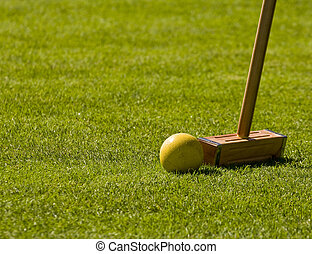 Croquet Mallet and Yellow Ball - A croquet mallet about to...