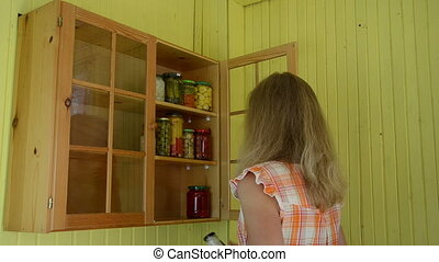 girl pickled food shelf - Girl put glass pots full of...