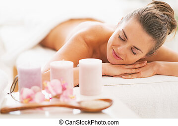 Closeup on spa therapy ingredients and relaxed young woman...