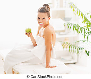 Smiling young woman with apple sitting on massage table