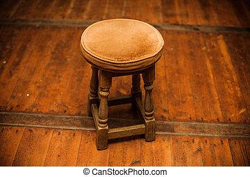 Antique stool on wooden floor