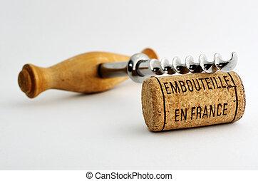 vintage old corkscrew and wine cork with inscription embouteille en France