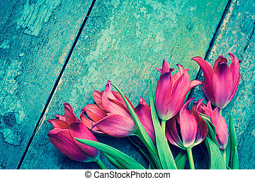 Red tulips on the rustic table