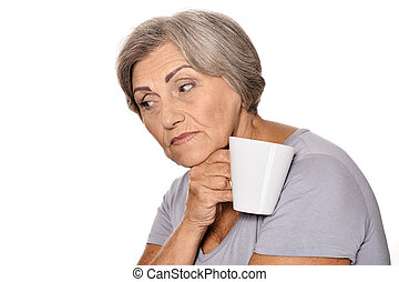 Thinking elderly woman with cup on white background