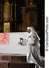 Nun ringing bells during consecration - Nun ringing copper...