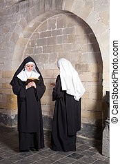 Two nuns in an old convent - Two young nuns passing...