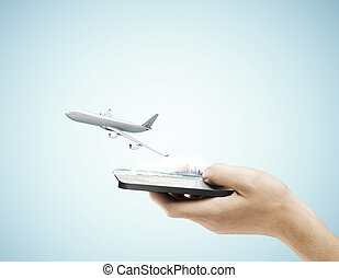 hand holding phone and airplane on a blue background