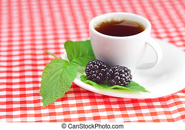 cup of tea and  blackberry with leaves on plaid fabric