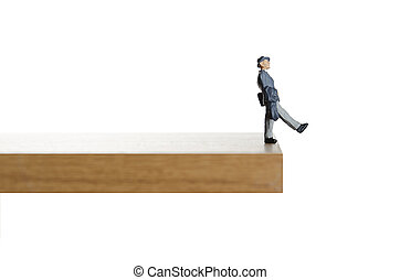 Walking on the edge. - Business figurine walking off a ledge...