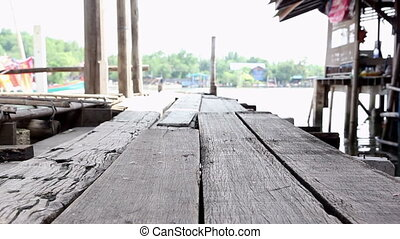 Traditional Thai wooden pier beside the river