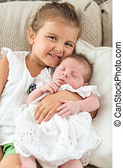 Baby girl wearing a dress in sister's arms - Newborn in...