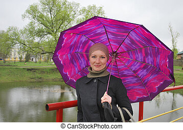 on the bridge near the lake is a girl with an umbrella.