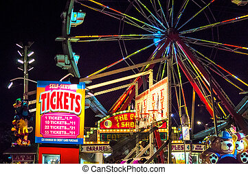 State Fair - A ferris wheel and ticket booth at night at a...