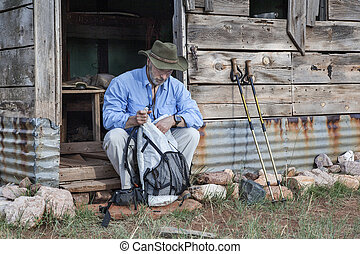 hiker and old mountain cabin - senior male hiker sitting...