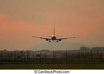 Plane Landing - Airliner landing against sunset sky