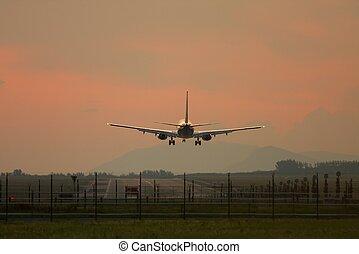 Plane Landing - Airliner landing against sunset sky