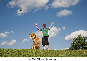 Boy Raising Arms - Little Boy on a Hill with his Dog