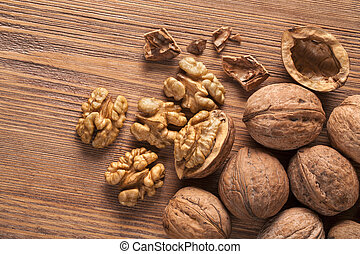 walnuts - Walnut kernels and whole walnuts on rustic old...