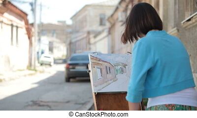 Girl artist painting picture on canvas of the old street in...