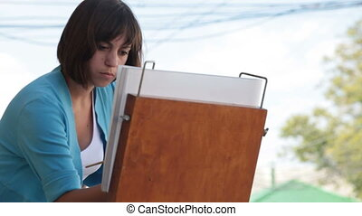 Girl artist painting picture on canvas