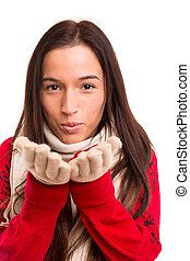 Asian Woman - Young asian woman dressed for winter blowing a...
