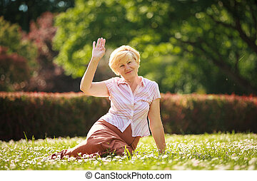 Maturity European White Hair Woman sitting on Grass and...