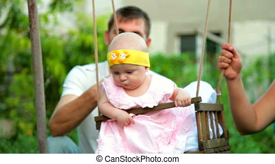 Family with baby on a swing in the garden