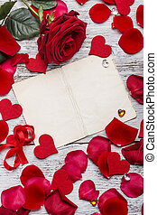 Red rose and petals with card with space for text