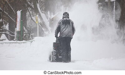Snow removing - Man operating snow removing machine in the...