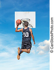 basketball in the sky - basketball player dunking with a sky...