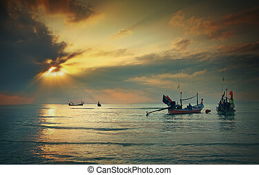 Longtail boat in the sunrise over sea and blue sky...