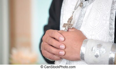 Hands of the priest with a crucifix