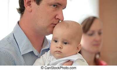 father with baby in her arms on ceremony of baptism - father...
